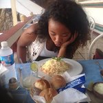 Daughter blowing on the hot shrimp alfredo.