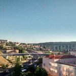 Vista dos quartos de trás do hotel: avião pousando (acima, à esq.) e aqueduto de Lisboa ao centr