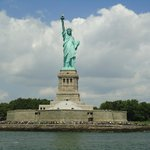 The statue, the island of liberty and the people who come to see it.
