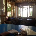 Nice restaurant in the shade of palm trees, with small tables and pillows to sit on.
