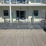 view from a room on a lower floor - you see decking and others sunbathing on the deck, but no se