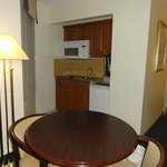 The kitchenette and table--cooktop, sink, microwave, fridge--stocked with dishes, pots, coffee,