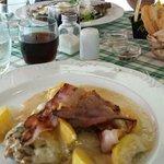 Costoletta di maiale con pesche e pancetta croccante in primo piano, in secondo tagliata rucola
