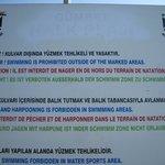 """афиша, гласящая о том, что пляж общественный, а не частный, как заявляют """"турки-собственники"""""""