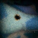 Cigarette burns on the blanket