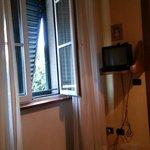 von Bett auf das doppelt verglaste Fenster mit grünen Läden. Rechts ein kleiner Fernseher.