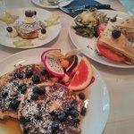 Hinten links: Cinnamon Roll (Nur am Wochenende), vorne links: Pancake mit Blaubeeren, rechts: To