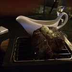 Perfectly cooked med-rare steak served on charcoal mini bbq