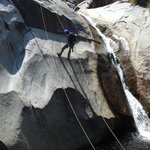 Rappelling next to a waterfall