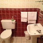 Salle de bain, avec lavabo, toilettes, baignoire, petits flacons de gel douche et shampoing.