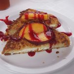 Corn flake crumbed french toast stuffed with marscapone and garnished with fresh peaches and a r