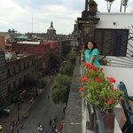 The spacious balcony with Centro Historico view, greenery and flowers, and furniture.