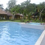 pool with jacuzzi with nipa hut houses on the background