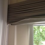 Curtains hanging off / second one stuffed in cupboard hiding electric box