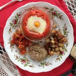 Egg baked in a tomato, with the remainder baked with basil