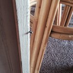 One of 3 nails sticking out at knee level on the corner of the kitchen cabinet.