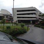 Бассейн справа от отеля , соединен с отели переходом .