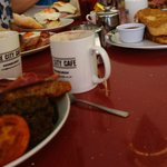 Full cooked breakfast with french toast, maple syrup and bacon behind