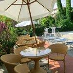 Tavoli, ombrelloni dietro i lettini della piscina