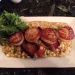 Seared day boat sea scallops on a bed of corn and tomatoes with crisps of pork. So delicious!