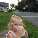 Daughter drinking lemonade on one of the large rocks (annex building and pool in background)