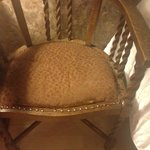 Dusty bedroom chair was covered with huge bedspread, extremely worn seating