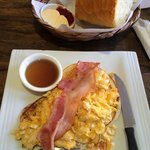 American pancakes with scrambled eggs, bacon, syrup, fresh bread with jam and butter (comes with