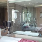 Room with a glass window to the bathroom