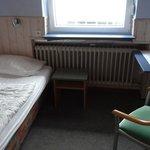 Zimmer mit Bett und Nachtschränkchen