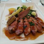 Honey glazed duck with foie gras, summer vegetables, and lavender sauce