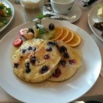 Blueberry pancakes with fruit and maple syrup