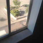Broken screen, stained windowsill in room.