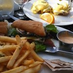 Breakfast sandwhich with ham, brie, apples and a side of fries. Eggs benedict in the background.