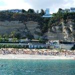 Blick von einem Boot auf den Strand und das auf den Felsen liegende Hotel
