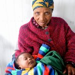 A grandmother caring for her grandchild at a senior center.