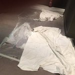 crumpled drop sheets and torn plastic in first floor corridor