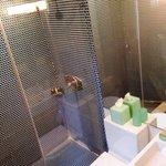 Banheiro com blindex, ducha com água fria/quente e amenidades.