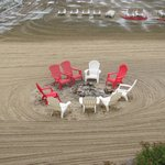Fire pit on beach with chairs on beach.