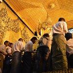 Putting gold leaf on the Buddha