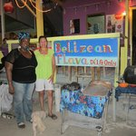 Taking a picture of the colorful sign and owner of the Belizean Flava Restaurant.