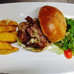 Aussie beef burger with bacon, cheese, pickle, garden salad and potato wedges.