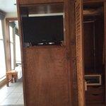 Fernseher,Kleiderschrank und Safe.dahinter das Bad