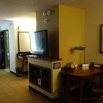 view of room towards bathroom showing large flatscreen TV & desk