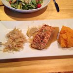 Salmon with butternut squash and slaw. In the background, Caesar Salad with Salmon.