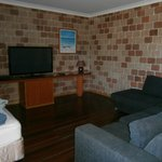 The very very large living room with a big flat screen and comfortable L shaped lounge.