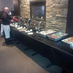 Chef Kevin re-stocking containers in chafing dishes