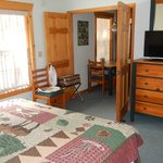 The bedroom with flat-screen TV, very cute bedspread, and bedside tables. The bathroom is @ the