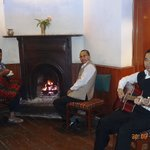 Krishna with the guitar and Mr. Uttam Paul next to him in front of the fireplace in the restaura
