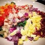 Cobb Salad with mixed greens topped with grilled chicken, avocado, tomatoes, red onions, egg, sm