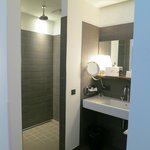 Sleek Shower / On the Opposite Side of the Sink is the Toilet Room
